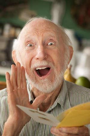 Senior man thuis lezen wens kaart