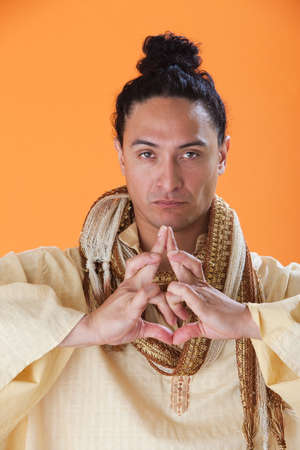 new age: Handsome New Age Guru Making a Strange Symbol with his hands Stock Photo