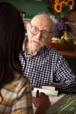 Elderly man in home with care provider or survey taker in kitchen Standard-Bild