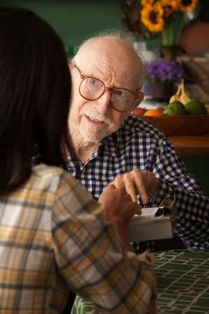 geriatric care: Elderly man in home with care provider or survey taker in kitchen Stock Photo