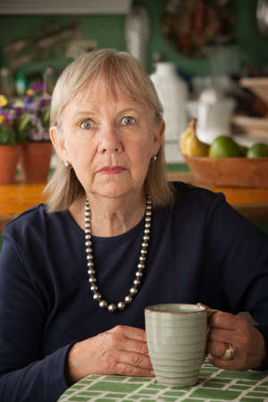 Depressed senior woman at home with coffee or tea photo