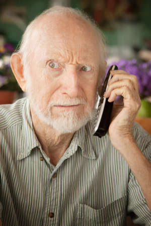 Grumpy senior man at home on the telephone photo