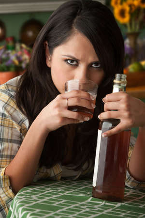 Alcoholic Latina Woman at Home with Liquor Bottle Stok Fotoğraf
