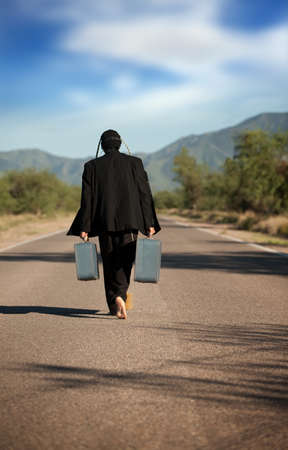 Strange indigenous man in the middle of a road with suitcases photo