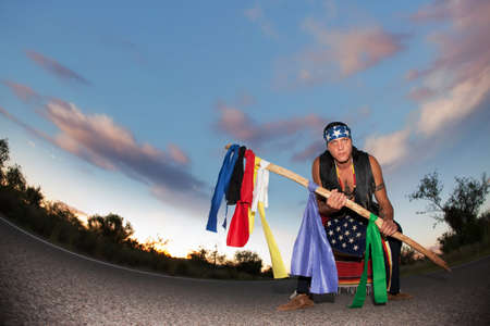 Indigenous man squatting in the middle of a road with ceremonial pole and flags in the middle of a road with ceremonial pole representing seven directions