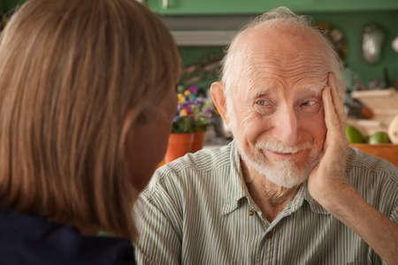 Senior pareja en su casa en cocina, centrándose en el hombre