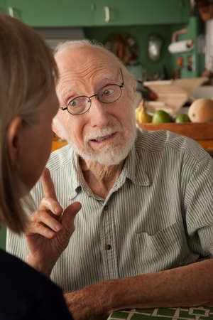 Senior couple at home in kitchen focusing on man photo