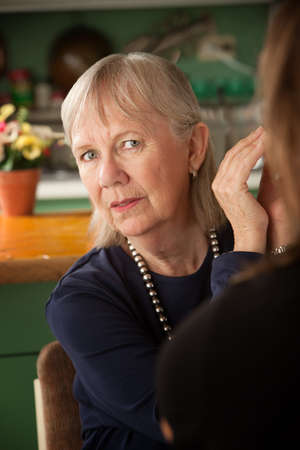 Senior woman in kitchen talking with daughter or friend photo