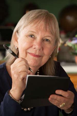 chequebook: Mujer Senior en casa con chequera  Foto de archivo
