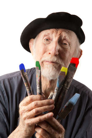 Eccentric senior artist with brushes wearing a beret photo