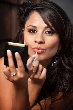 gloss: Beautiful Latina Woman Looking into Compact Mirror and Applying Lip Gloss