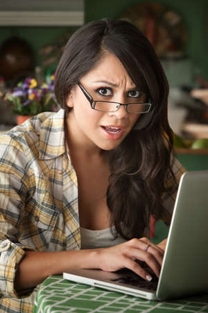 Shocked Beautiful Latina Woman at table in Kitchen with Computer photo
