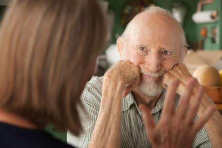 Senior paar thuis in keuken gericht op boze man  Stockfoto