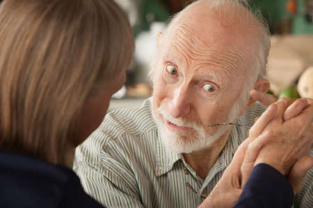Senior couple at home in kitchen holding hands focusing on man photo