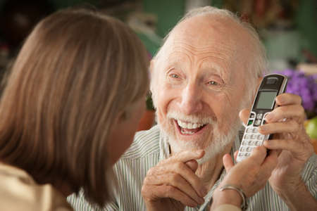 Senior couple at home with a telephone photo
