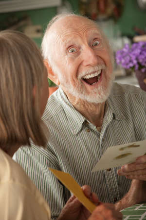 Senior man at home reading greeting card with wife photo