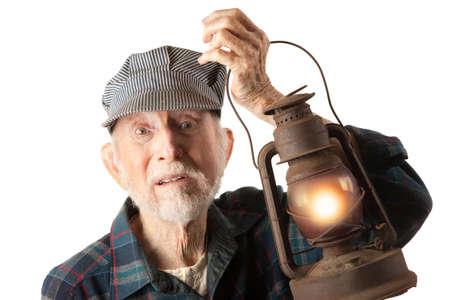 apprehensive: Apprehensive railroad man holding a glowing red lantern. Stock Photo