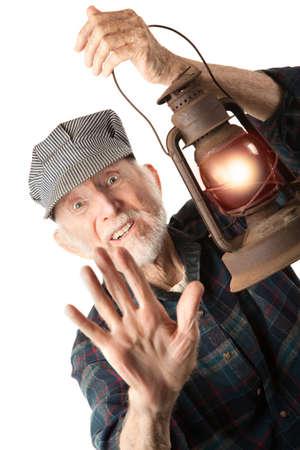 Apprehensive railroad man holding a glowing red lantern.