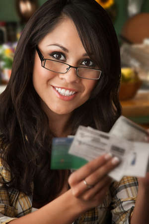 Beautiful Latina Woman at table in Kitchen with Coupons