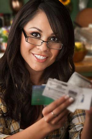 Mooie Latina vrouw aan tafel in de keuken met Coupons  Stockfoto