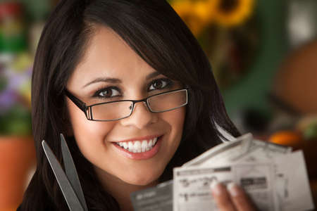 coupon: Beautiful Latina Woman at table in Kitchen with Coupons