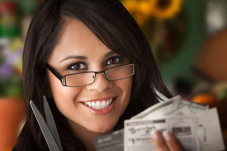 Mooie Latina vrouw aan tafel in de keuken met Coupons