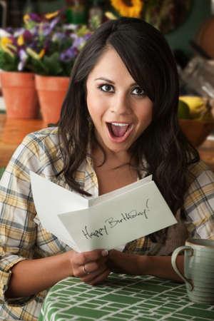 Beautiful Latina Woman at Table in Kitchen Birthday Card Stock Photo