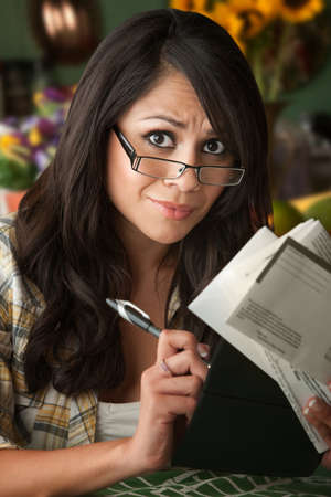 household money: Beautiful  Latina Woman at Table in Kitchen with Many Bills Stock Photo