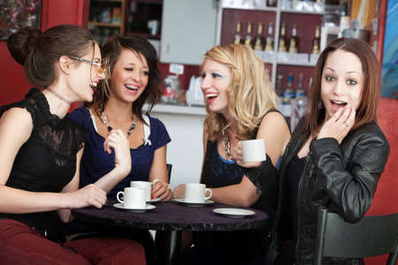 Teenaged girl surprised about what her friends are saying at a café photo