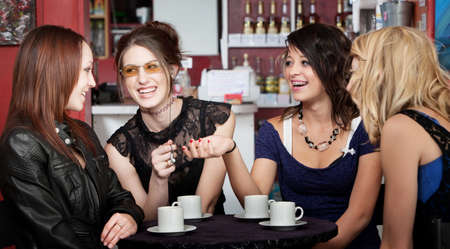 chat: Four female students teasing one another over coffee at a cafe