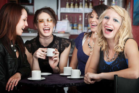 Pretty young blonde laughing with three friends in a cafe