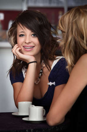 A cute teenaged girl with braces sitting at a table with a friend. photo