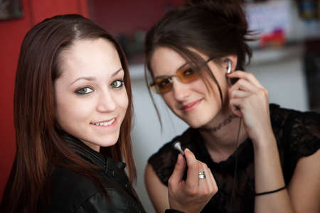 earphone: A cute teenager sitting with a friend removing her earphone at a cafe