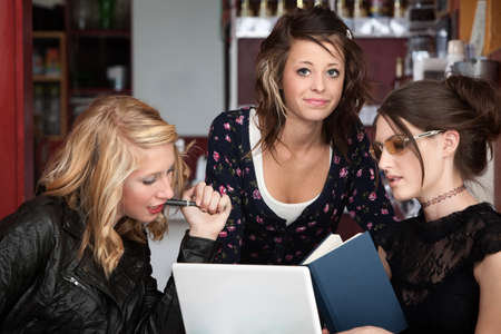 Three female college students studying with a book and laptop in a cafe Archivio Fotografico