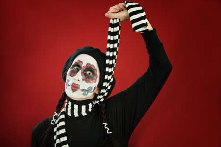 A Woman Ties her Neck with a Striped Scarf on All Saints Day