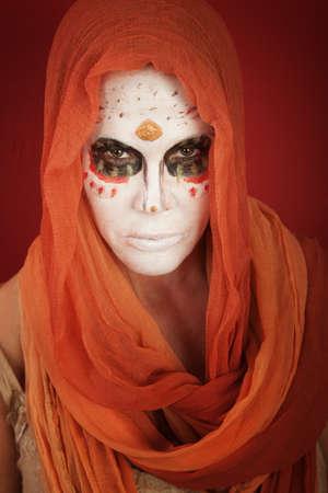 Een dame met dramatische alle zielen dag make-up en een oranje sjaal