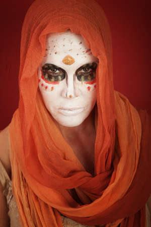 A lady with dramatic All Souls Day makeup and a orange scarf