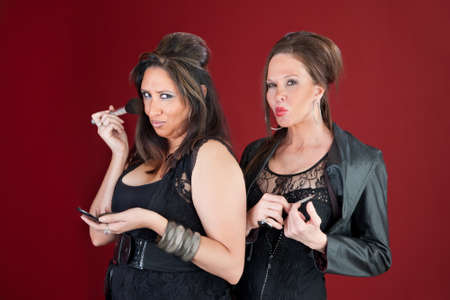 Two sexy middle-aged New Jersey style housewives dressed in black prepare their makeup Фото со стока