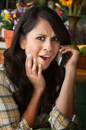 Frustrated Latina Woman on Phone  Waiting for Service or taking Sales call photo