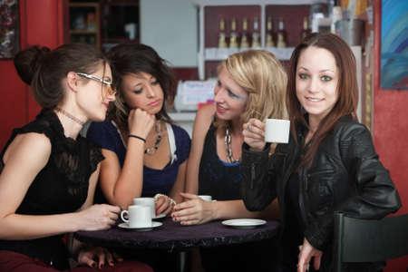 自信を持って若い女性は、カフェで友人とコーヒーを飲む