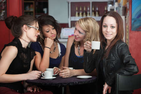 A confident young woman drinks coffee with friends in a cafe Stock fotó