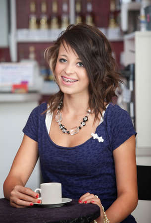 A cute, young teenage girl with braces smiling in a cafe photo