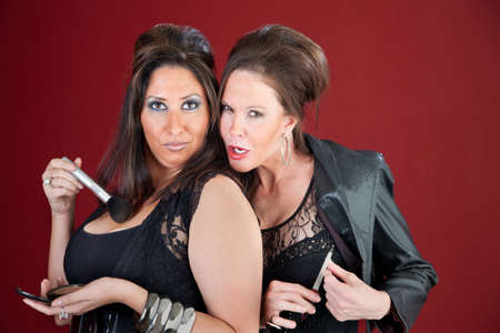 Two cougers dressed in black tease each other and prepare their makeup photo