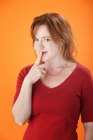 A middle-aged sexy woman with her finger to her lips photo