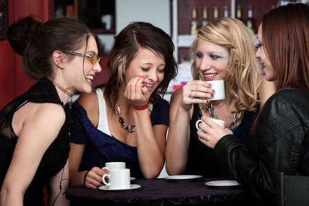 chat: A foursome of pretty girls laughing in a cafe