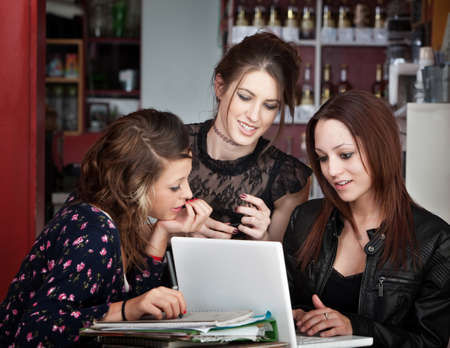 Three cute female students studying with a book and laptop in a cafe photo