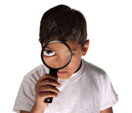 Young Latino boy looking through a magnifying glass on white background photo