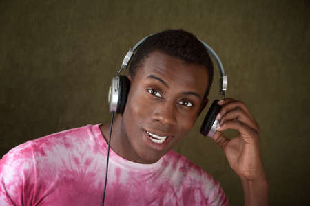 Young African-American Man Listening to Music on Large Earphones Imagens
