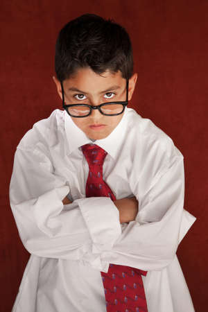 Cute young boy in his fathers shirt and eyeglasses photo