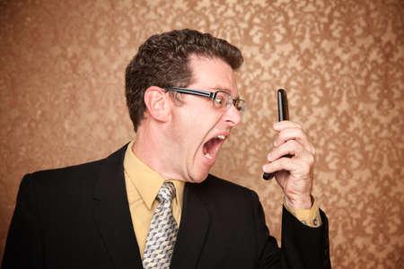 ipertensione: Arrabbiato Business Man gridare al suo telefono cellulare Archivio Fotografico